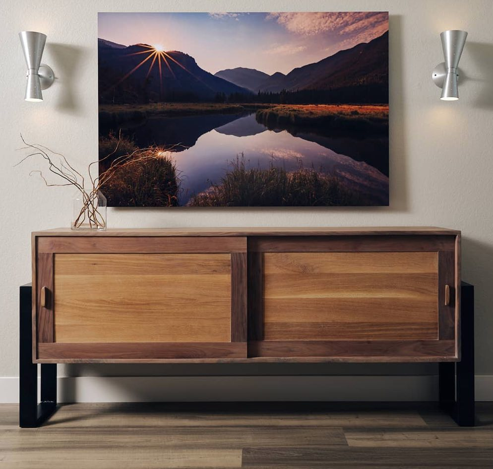 an Ethos storage chest or credenza with sliding doors and contrasting wood trims. Over the cabinet is a photo of a mountain lake at sunrise