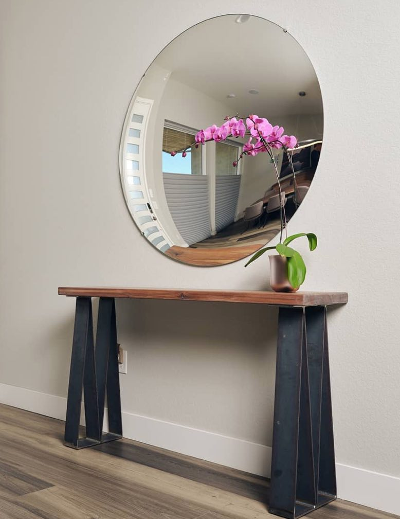 Ethos console with wooden slab top and triangular black stee; supports, topped by a large round mirror and a fuschia orchid