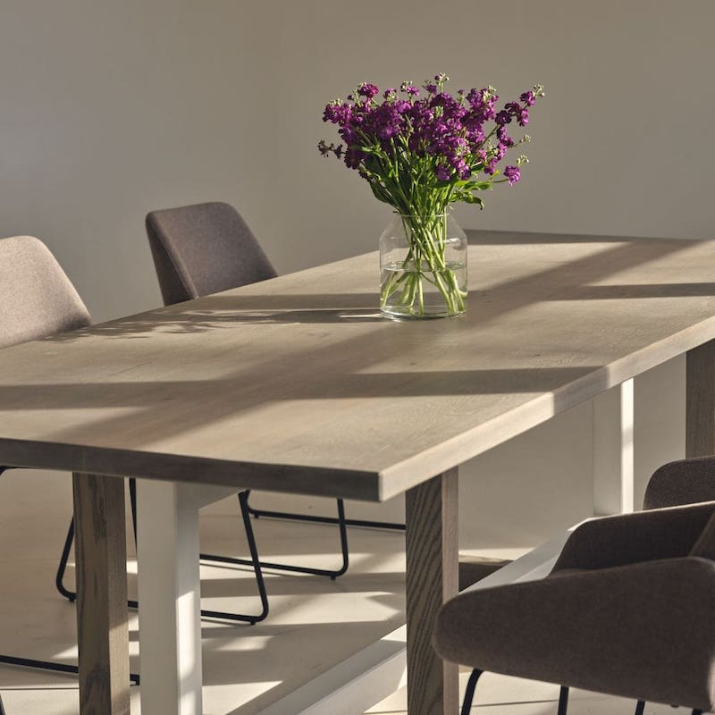 wooden dining table in rectangular shape with a light finished top, and straight wooden legs. A vase of purple flowers is on the table.