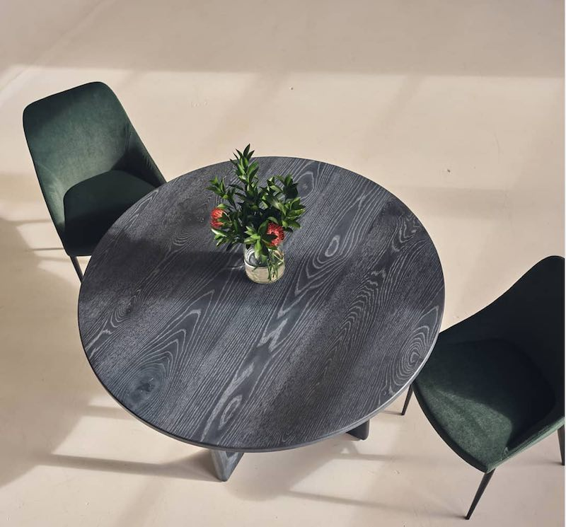 Ethos small round dining table with dark finish and prominent grain, birds-eye view