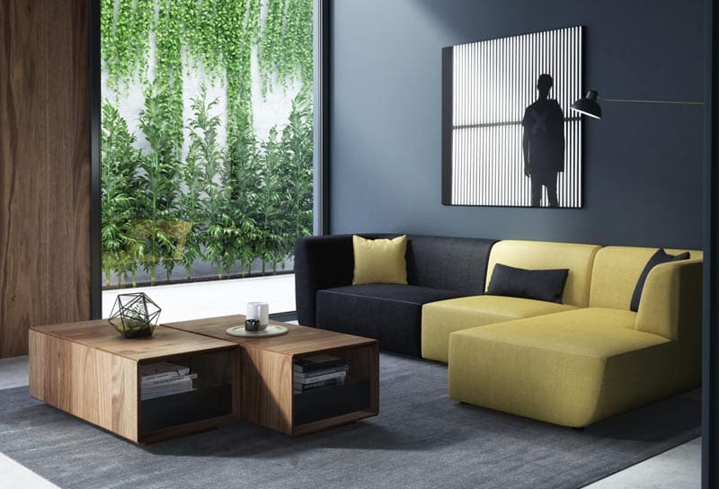 a blocky yellow and black sectional sofa with an ivy-covered wall