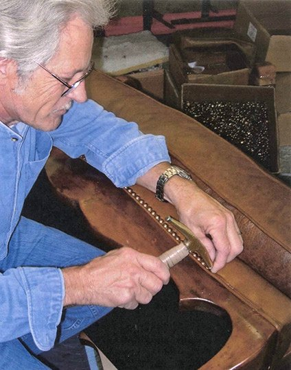 An artisan hammers in a row of nail heads for a leather and wood sofa
