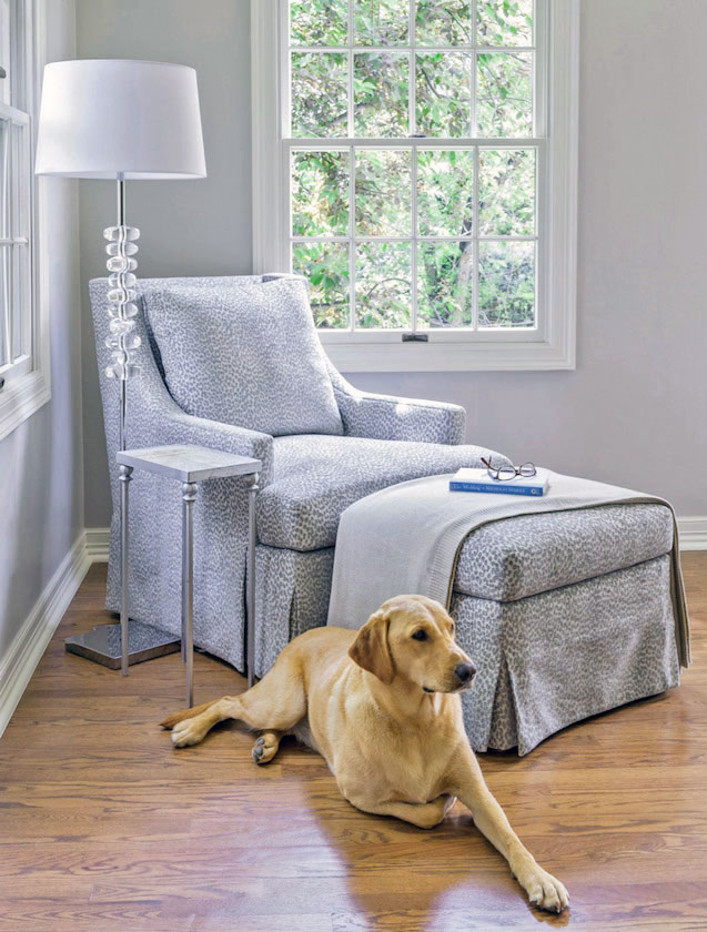 a slip-covered chair and ottoman by Design Wright Studios make for a cozy reading area by a window