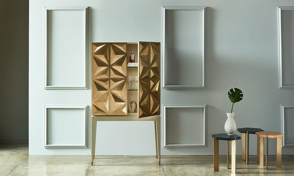 a white paneled room with a sculptural wine storage cupboard in a brass finish, by Antonia