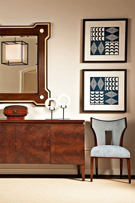 fine furniture by EJ Victor, with a beautiful sideboard made from grained mahogany, a curved side chair, and tribal art
