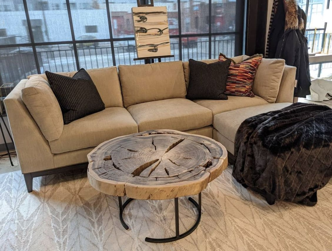 Design Wright Studios' 590 sectional sofa in creamy dark beige upholstery with throw pillows and a live-edge slab coffee table