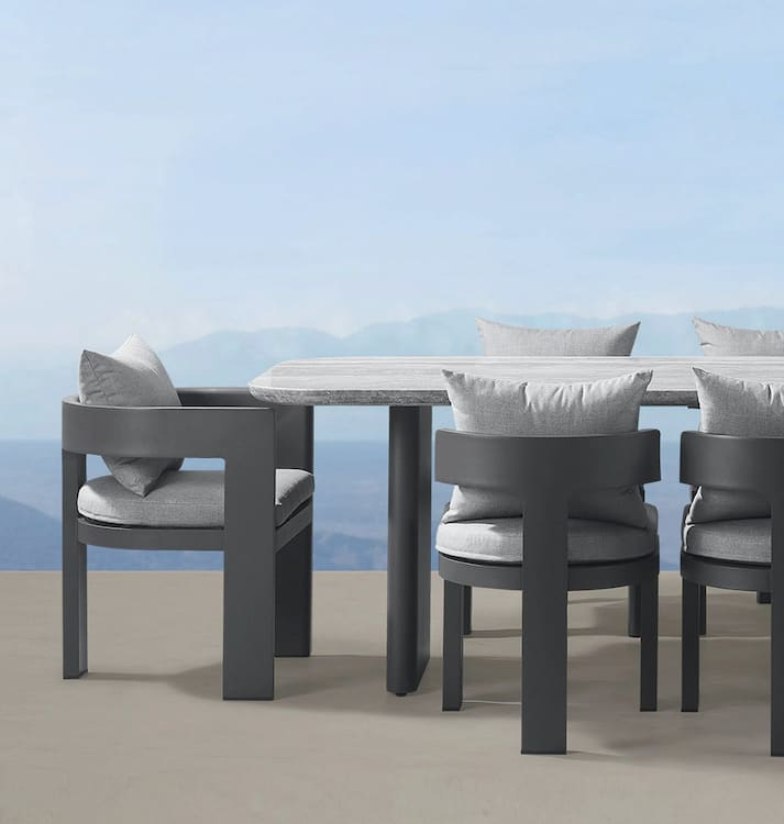 dining set by Harbour Outdoor, with grayed wooden T-back chairs and cushions, overlooking an expansive landscape
