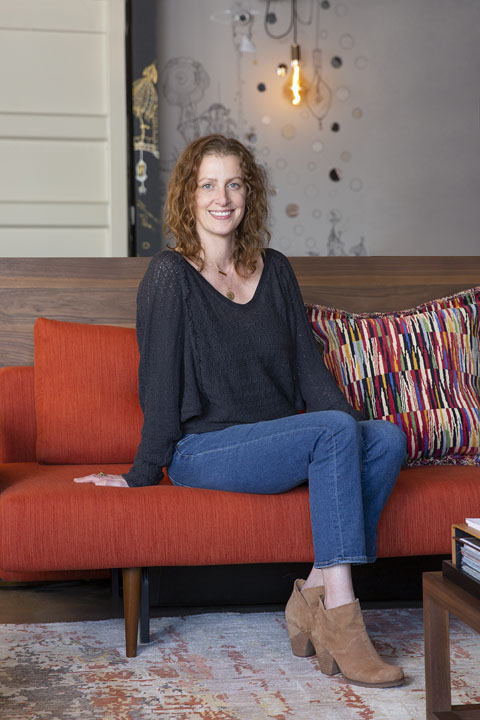 Heather Kelly smiling on a dark orange sofa
