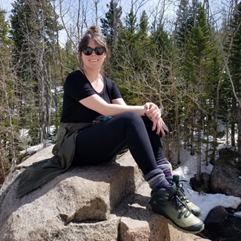 Alyssa in hiking boots, sitting on a rock in the mountains